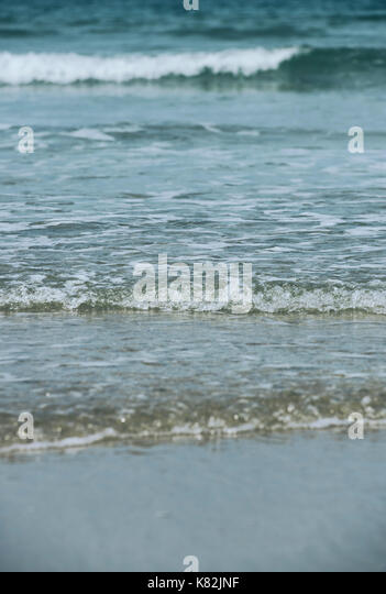 The sea gently breaking onto a sandy beach - Stock Image