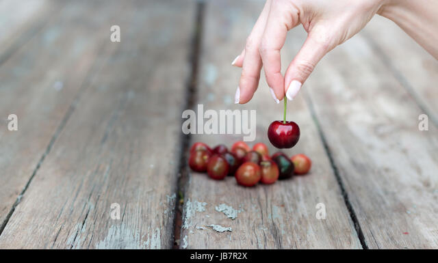 A female hand is selecting a cherry from a wooden table. - Stock Image