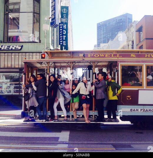 Tourists ride a cable car in downtown San Francisco. - Stock Image