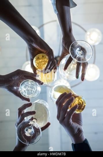 Group of friends making a toast, upward view of hands holding glasses - Stock-Bilder