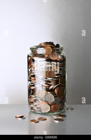 Change jar overflowing on counter - Stock Image