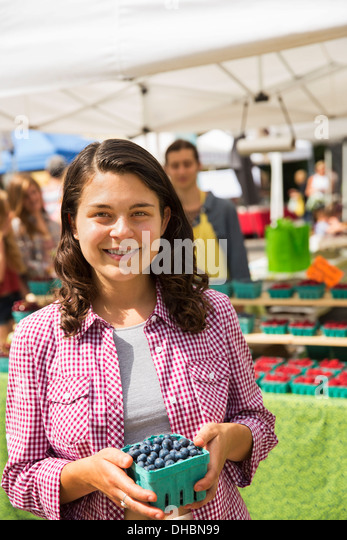 A young girl at a farm stand holding a punnet of blueberries. - Stock Image