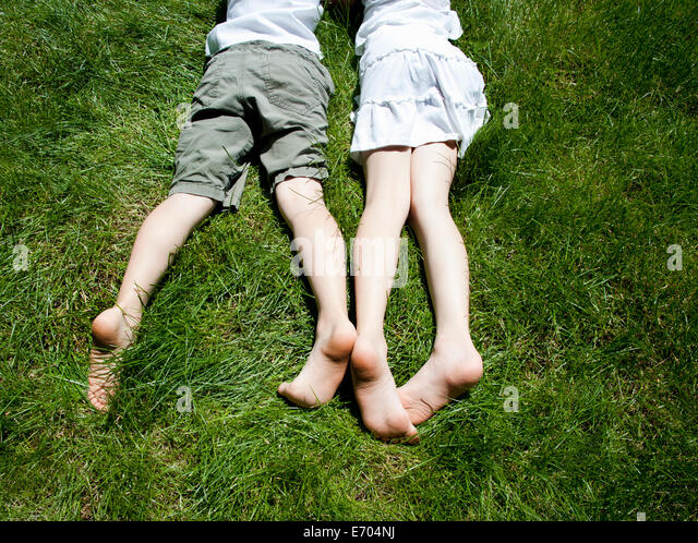 Overhead view of brother and sisters legs as they lay on grass - Stock-Bilder