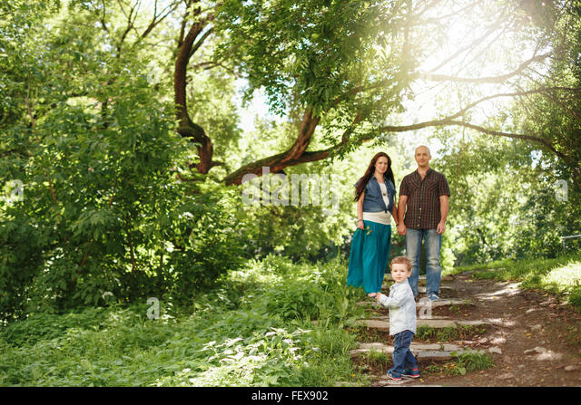 Happy Family Having Fun Outdoors. Pregnant Woman, Man and Cute Little Boy. Natural Colors. Selective Focus on a - Stock-Bilder