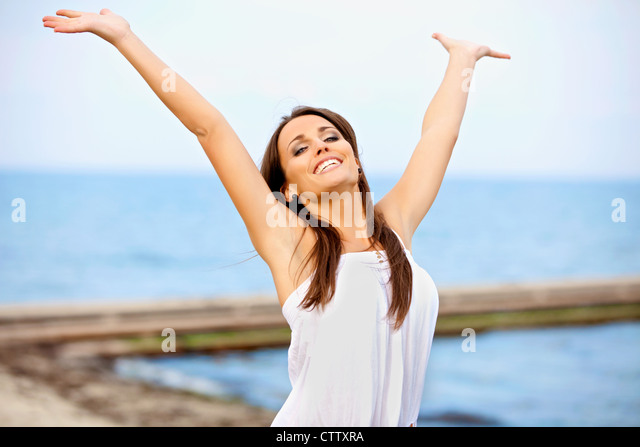 Cheerful woman with arms raised above her head - Stock Image