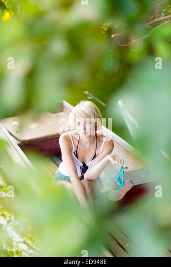 Woman relaxing on the vintage wooden boat. - Stock Image