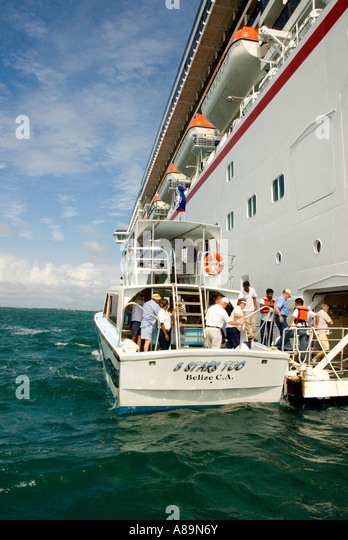 cruise ship passengers board tender ferry Belize City Central Latin America excursion transportation risky transfer - Stock Image