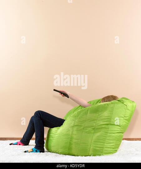 Pre teen girl in bean bag chair with tv remote - Stock Image