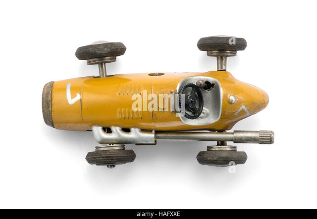 Vintage yellow toy racing car , top view on white background with natural shadow - Stock Image
