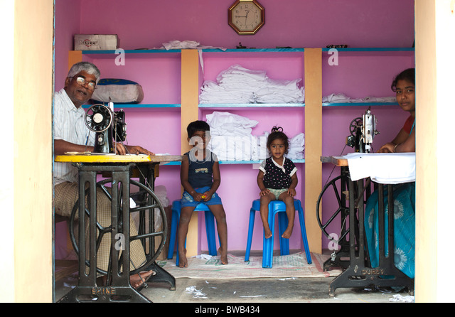 India family in their sewing shop in a rural indian village. Andhra Pradesh, India - Stock Image