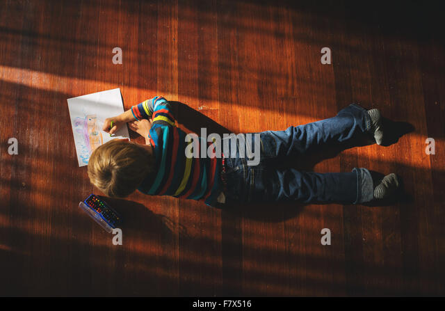 Overhead view of a boy lying on floor drawing a picture - Stock Image