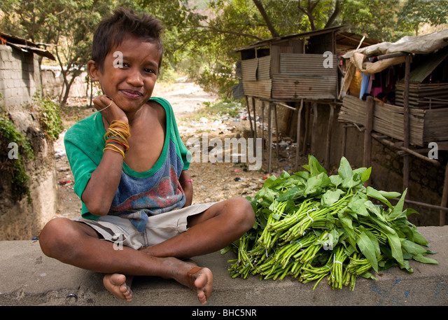 Cheeky Timorese boy sells vegetables on a bridge on the road to Dili East Timor - Stock Image