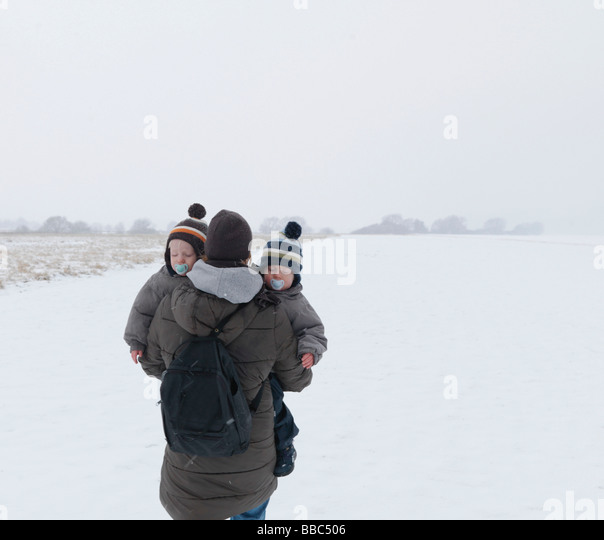 Woman walking with twin sons in snow - Stock-Bilder