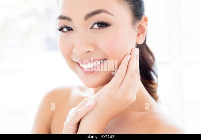 MODEL RELEASED. Young Asian woman with hands touching face, portrait. - Stock-Bilder