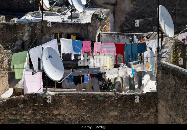 Over the rooftops view of Fez. Showing satellite dishes rows of washing hung out, derelict Riads, grass growing - Stock Image