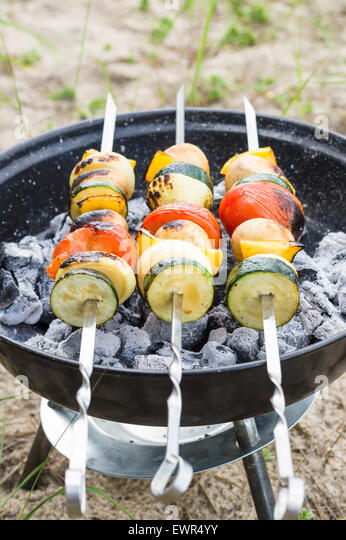 Vegan shish kebab on skewer. Fresh vegetables prepared on a grill charcoal, outdoors. - Stock Image