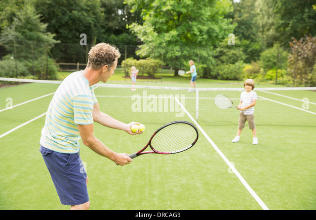 Family playing tennis on grass court - Stock Image