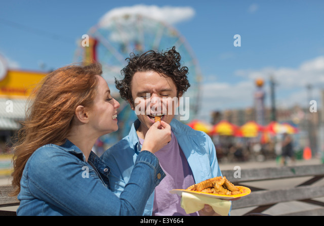 Romantic couple feeding each other chips at amusement park - Stock-Bilder