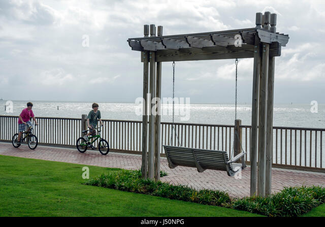 Point Clear Alabama Grand Hotel Marriott Resort hotel lodging Mobile Bay boys bicycle swing love seat - Stock Image