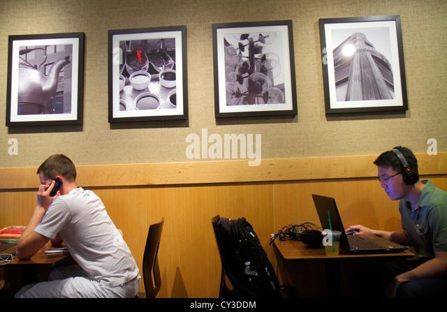 Boston Massachusetts Cambridge CambridgeSide Galleria Starbuck's Coffee Asian man laptop computer wireless wifi - Stock Image