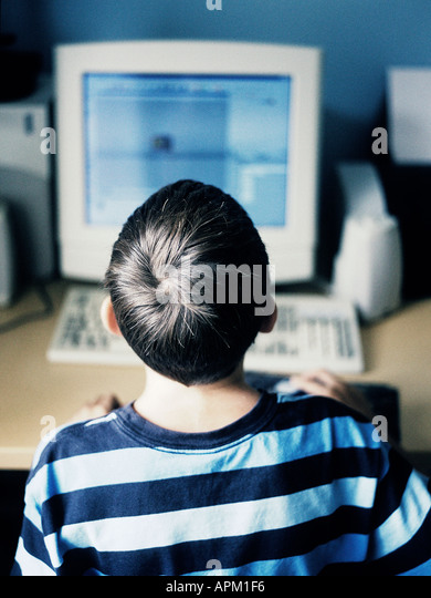 rear view of a child using a computer - Stock-Bilder
