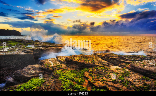 Warm colourful sunlight sheds on sandstone rocks and seaweed around eroded crack at sunrise time near Narrabeen - Stock Image