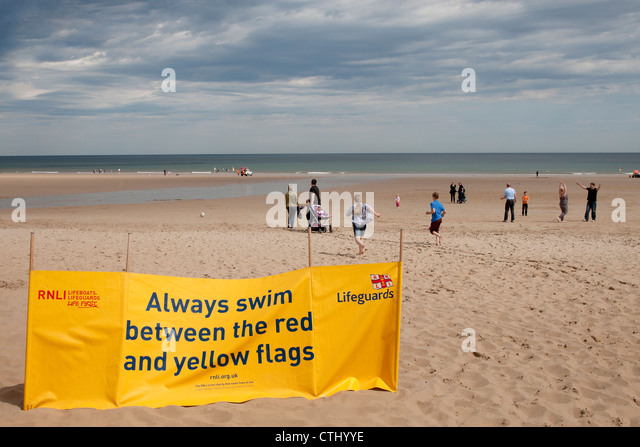 RNLI sign indicating need to swim between red and yellow safety flags, Tynemouth longsands beach, Tynemouth, england, - Stock Image