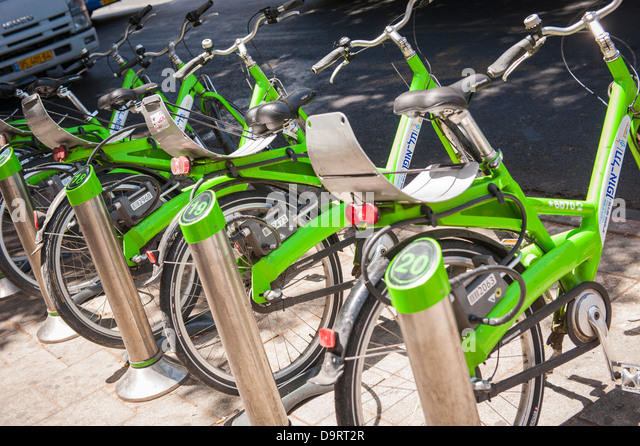 Israel , Tel Aviv Tel O Fun bright green self service bike bikes bicycle bicycles hire stand dock docking stands - Stock Image