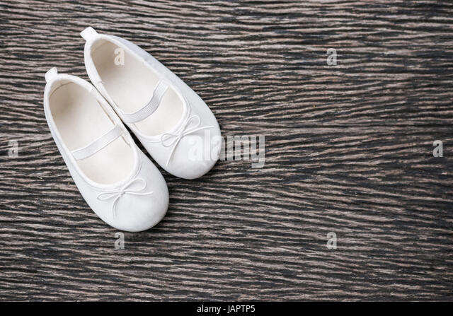 White baby shoe on wooden background , top view - Stock Image