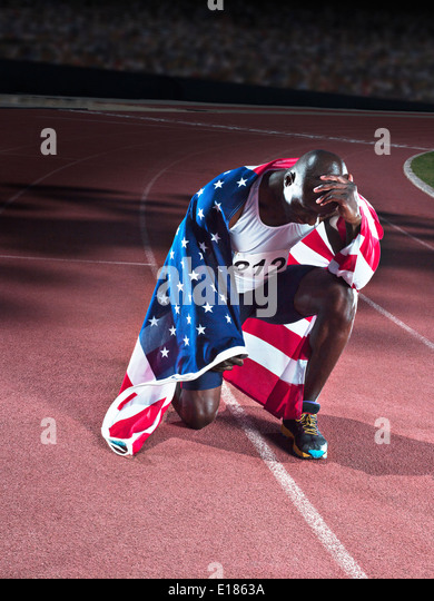 Track and field athlete wrapped in American flag on track - Stock Image