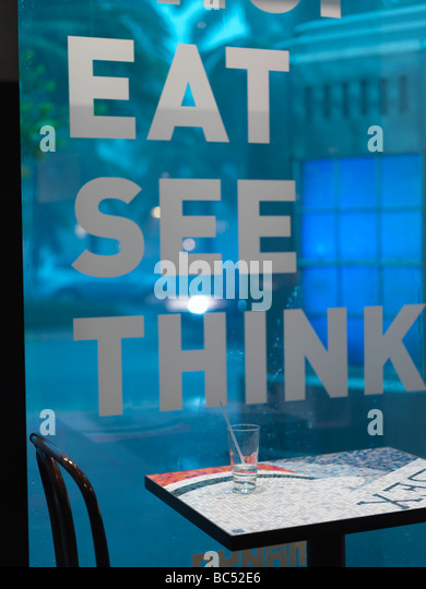 cafe table beside a window with the words eat, see, think - Stock-Bilder