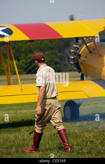 A pilot walks past a biplane taking off at the Flying Circus exhibition, Bealeton, Virginia. - Stock Image