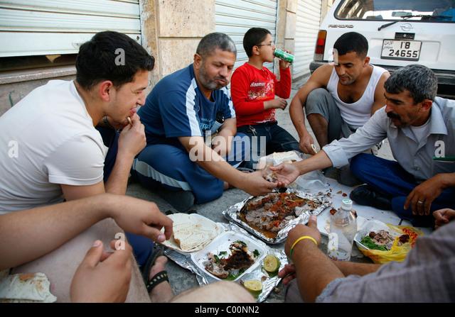 People eating togther on the street, Aqaba, Jordan. - Stock-Bilder