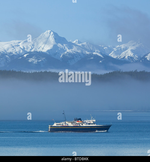 Alaska Marine Highway Ferry cruises through the mist, Inside Passage with snowcovered peaks in the background, Alaska - Stock Image