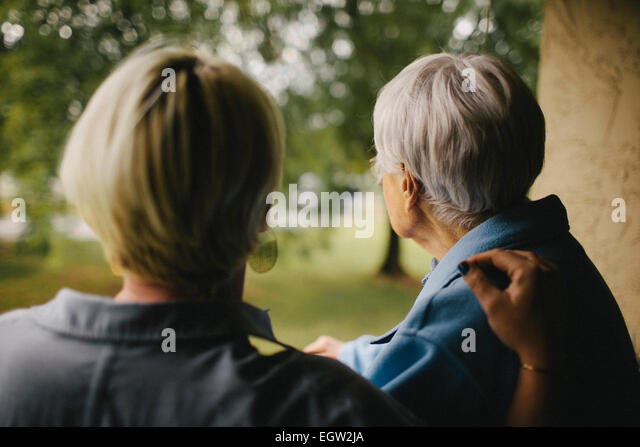 Younger woman's hand on senior woman's shoulder. - Stock-Bilder