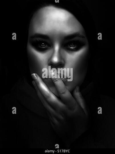 Dark portrait of young woman touching face - Stock-Bilder