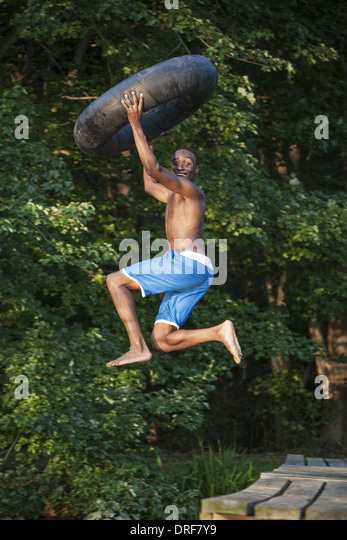 Maryland USA person boy holding swim float tyre leaping lake - Stock Image