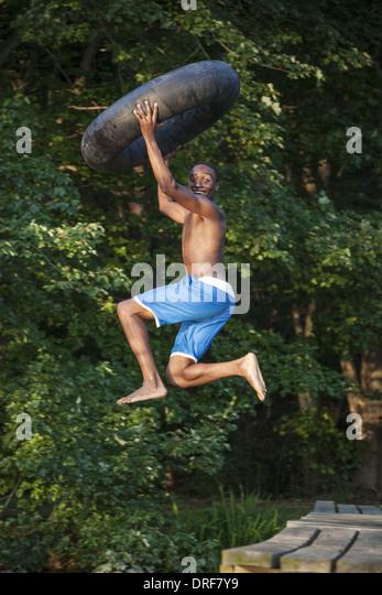 Maryland USA person boy holding swim float tyre leaping lake - Stock Image