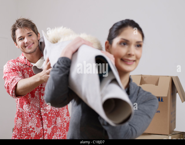 Couple with carpet over their shoulders - Stock-Bilder