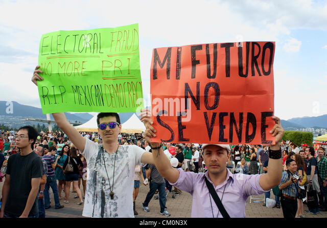 Mexican political protesters holding up signs at the Mexico Fest Mexican independence day celebrations in Vancouver, - Stock Image