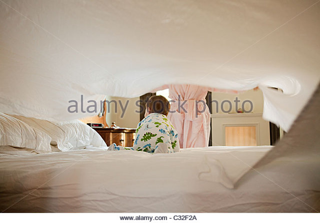 Mother and baby son making bed - Stock-Bilder