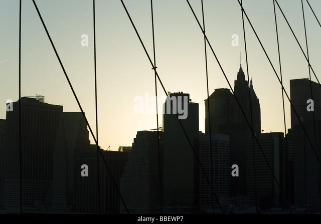 United States, New York City, silhouette of Manhattan skyline seen through Brooklyn Bridge - Stock Image