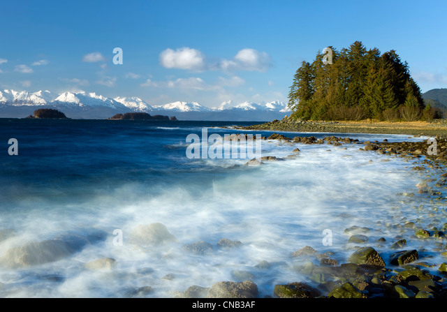 COMPOSITE: Wind and waves pound the rocky coastline along Eagle Beach, Lynn Canal, Inside Passage, Alaska - Stock Image