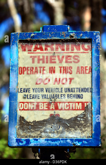 Old public sign at Haruru Falls parking area warning to lock their vehicles in case of thieves. - Stock Image