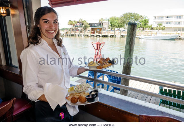 South Carolina SC Mt. Pleasant Shem Creek waterfront R.B.'s Seafood Restaurant dining woman waitress job carrying - Stock Image