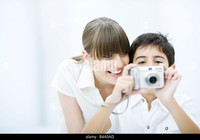 Boy taking picture with camera, mother leaning over his shoulder, smiling - Stock Image