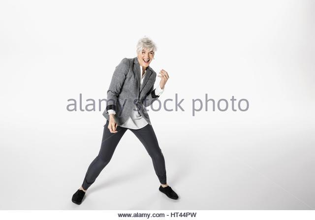 Portrait playful, energetic senior woman dancing against white background - Stock-Bilder