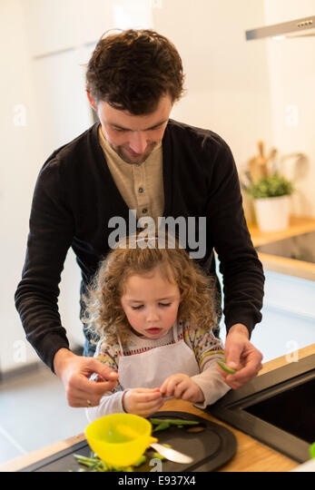 Father and his daughter preparing food - Stock Image