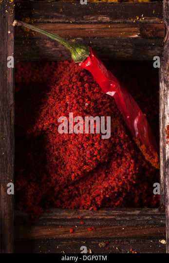 Top view on red hot chili pepper and ground paprika in old wooden box - Stock Image