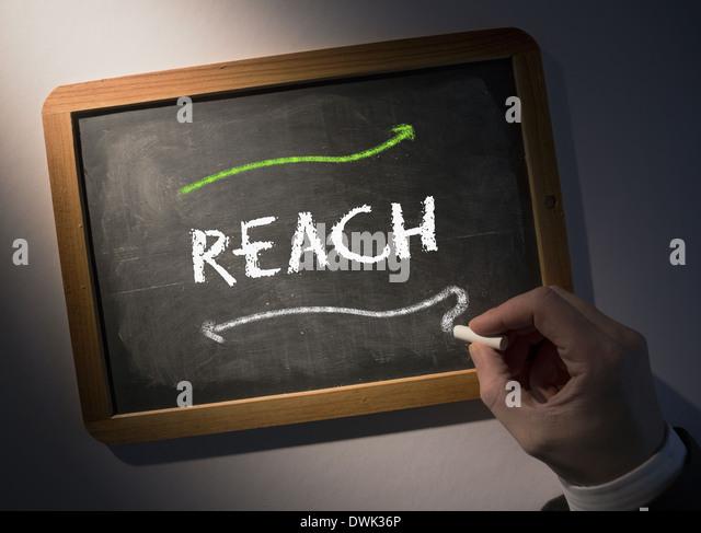 Hand writing Reach on chalkboard - Stock Image